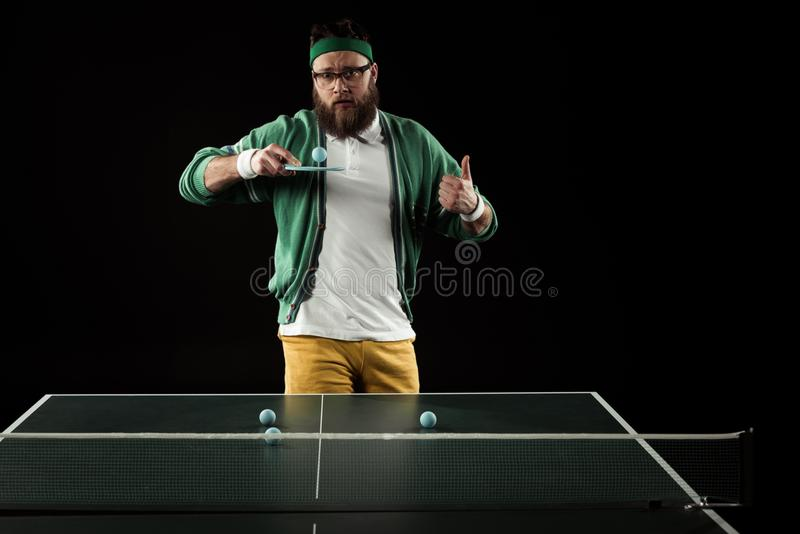 Bearded tennis player showing thumb up while practicing in tennis. Isolated on black royalty free stock photo