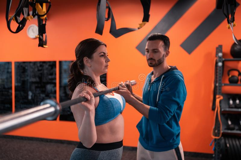 Bearded trainer assisting plump woman with lifting barbell royalty free stock photo