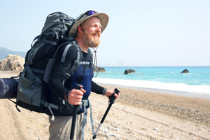 Bearded traveler with a backpack on the beach enjoys the beautiful scenery. The bearded traveler with a backpack on the beach enjoys the beautiful scenery stock photo