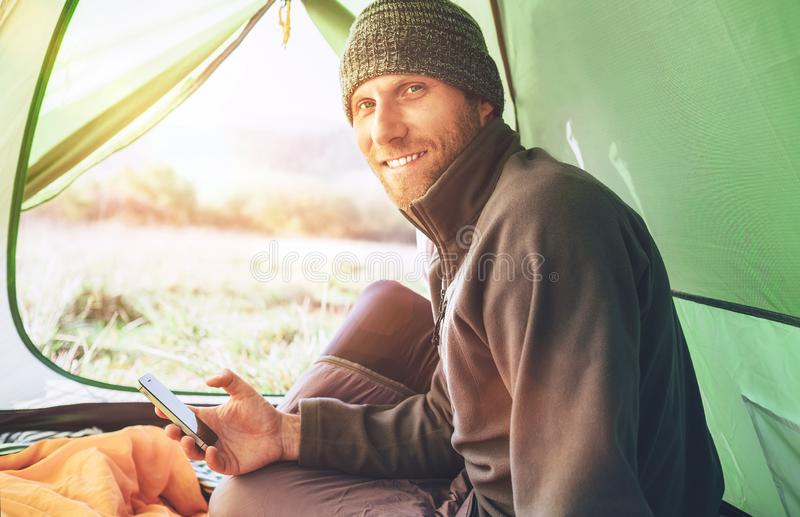 Bearded traveler Man uses his mobile phone sitting in tent royalty free stock images