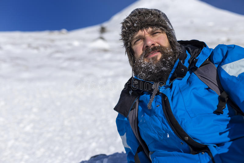 Bearded trekker resting while climbing in winter. Season royalty free stock photography