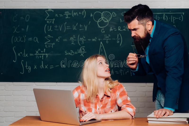 Bearded tutor helping his student. Students campus education knowledge concept. Teacher and student sit together at. Education class. Student and teacher stock image