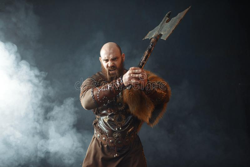 Bearded viking with axe enters the battle. Barbarian image. Ancient warrior in smoke stock image