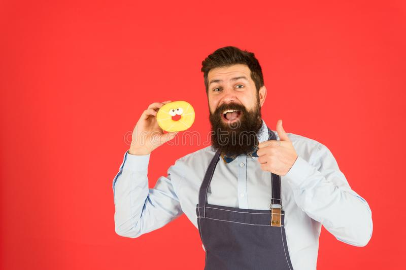 Bearded well groomed man in apron selling donuts. Donut food. Hipster baker hold donuts. Cheerful mood. Doughnut stock images