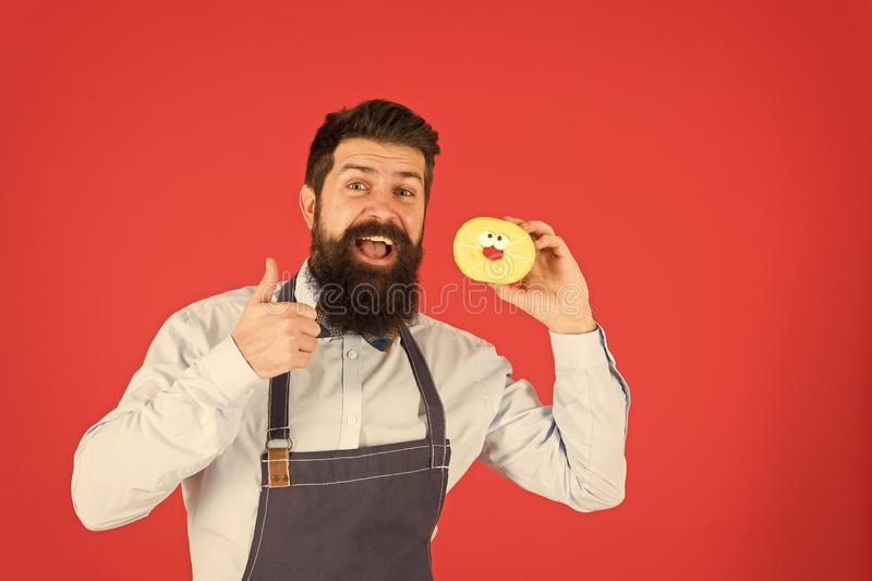 Bearded well groomed man in apron selling donuts. Donut food. Hipster baker hold donuts. Cheerful mood. Doughnut. Calories. Glazed donut. Baked goods. Sweets royalty free stock images