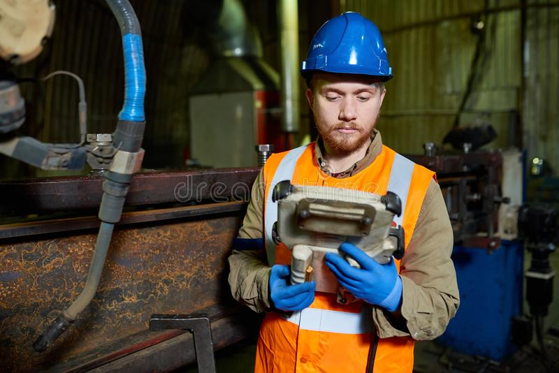 Bearded Worker Operating Machine. Waist-up portrait of handsome bearded worker wearing protective helmet and reflective vest operating machine at production stock images