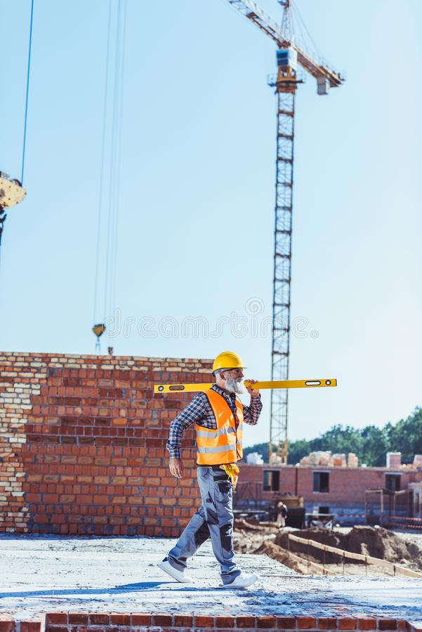 Bearded worker in reflective vest and hardhat walking with spirit level across stock photo
