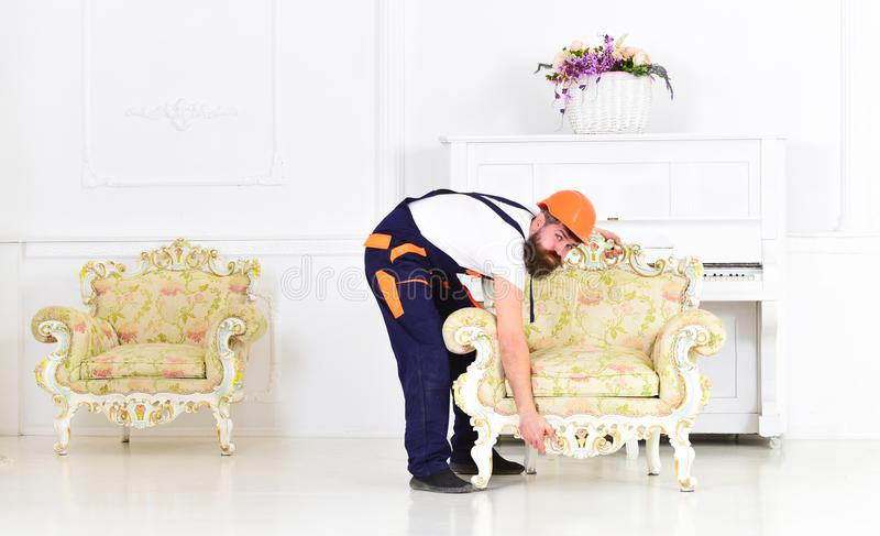 Bearded worker trying to lift heavy retro armchair. Packing the furniture and moving to new place royalty free stock image