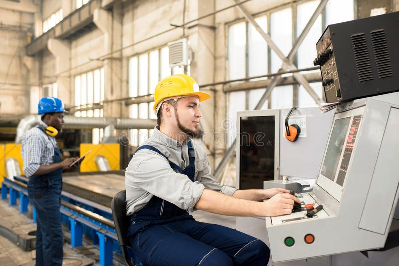 Working Process at Production Department. Bearded worker wearing protective helmet and overall operating machine while his African American colleague controlling royalty free stock image