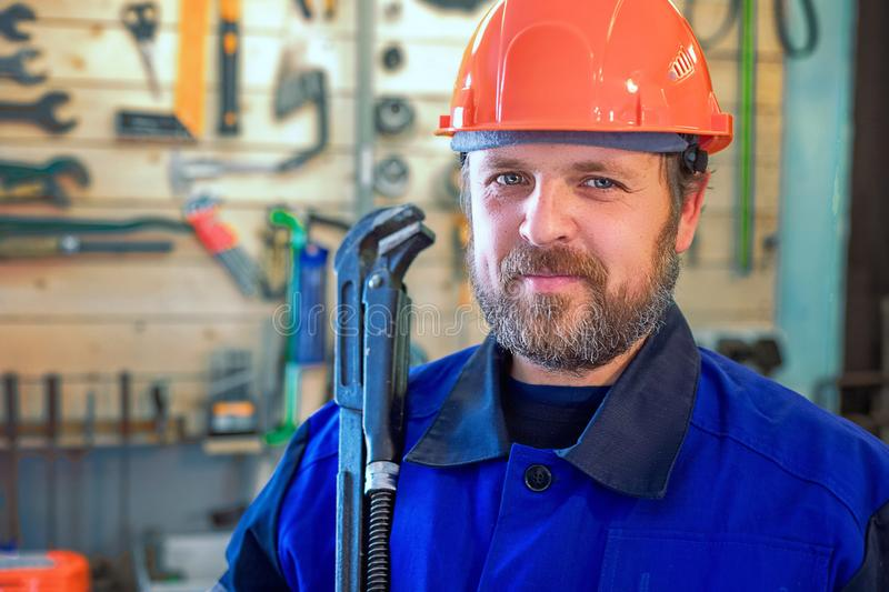 Bearded working plumber with large wrench in hand stock image
