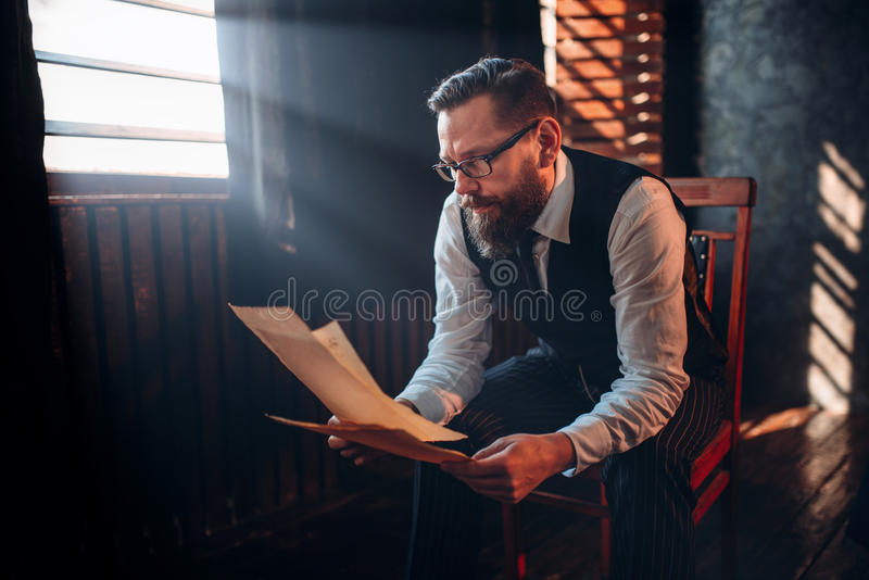 Bearded writer in glasses reads handwritten text stock photography