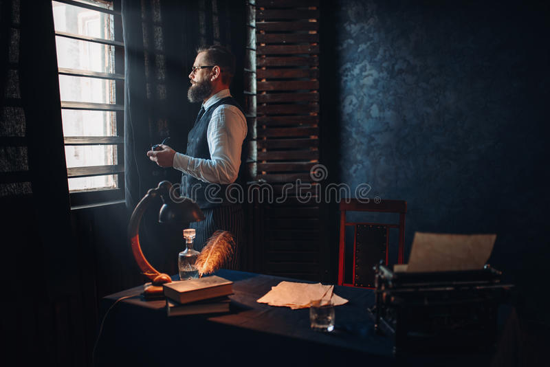 Bearded writer in glasses smoking a cigarette royalty free stock image
