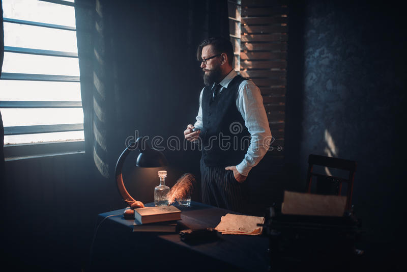 Bearded writer in glasses smoking a cigarette royalty free stock photo