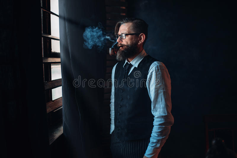 Bearded writer in glasses smoking a cigarette stock photo