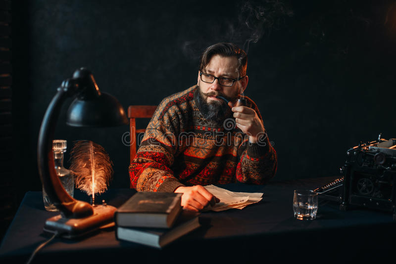 Bearded writer in glasses smoking a pipe royalty free stock image