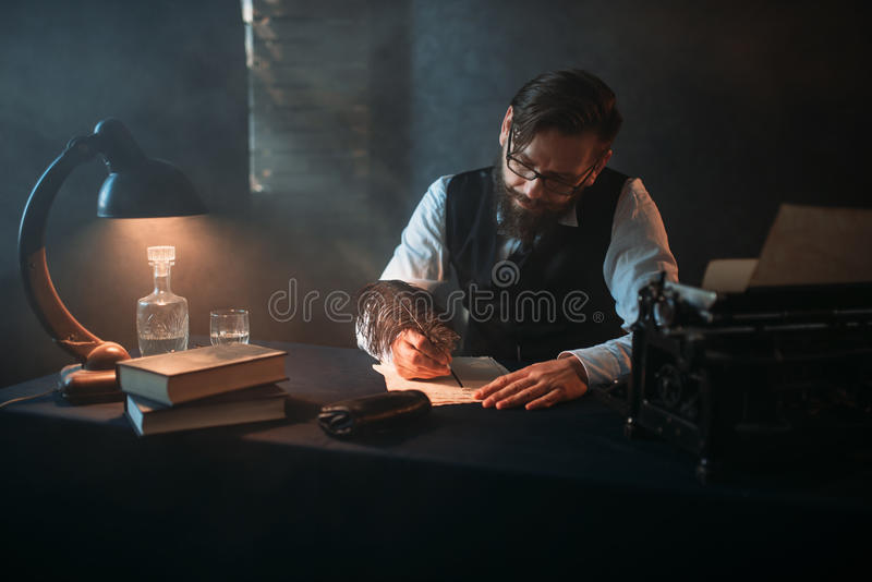 Bearded writer in glasses writes with a feather stock images