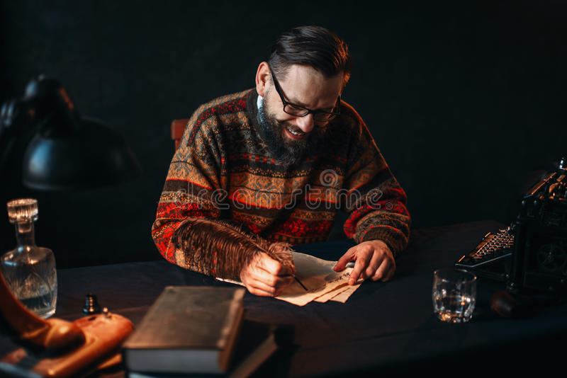 Bearded writer in glasses writes with a feather royalty free stock photo