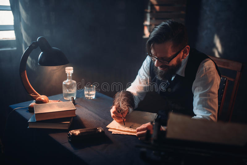 Bearded writer in glasses writes with a feather royalty free stock photography