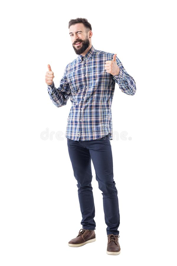 Bearded young adult business man in checked shirt with thumbs up smile and wink at camera royalty free stock photography