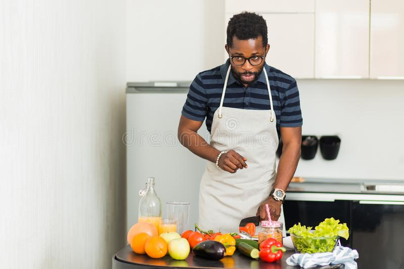 African man preparing healthy food at home in kitchen royalty free stock images