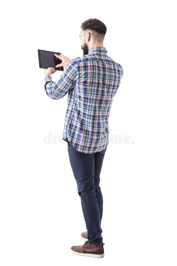 Bearded young business man pinching tablet touch screen with finger to resize. Full body isolated on white background royalty free stock photo