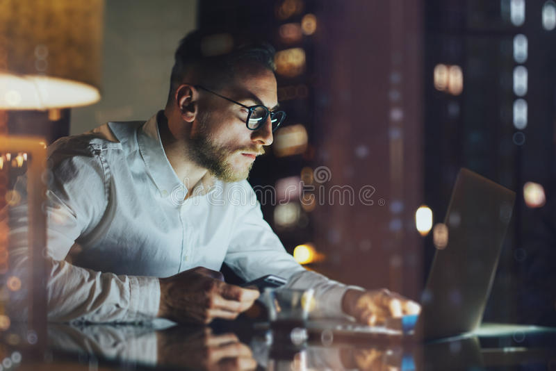 Bearded young businessman working on modern loft office at night. Man using contemporary notebook texting message, holding smartph. One, bokeh background stock photos