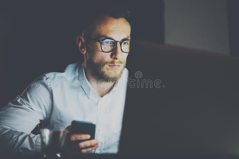 Bearded young businessman working on modern loft office at night.Man using laptop and smartphope, blurred background royalty free stock photo
