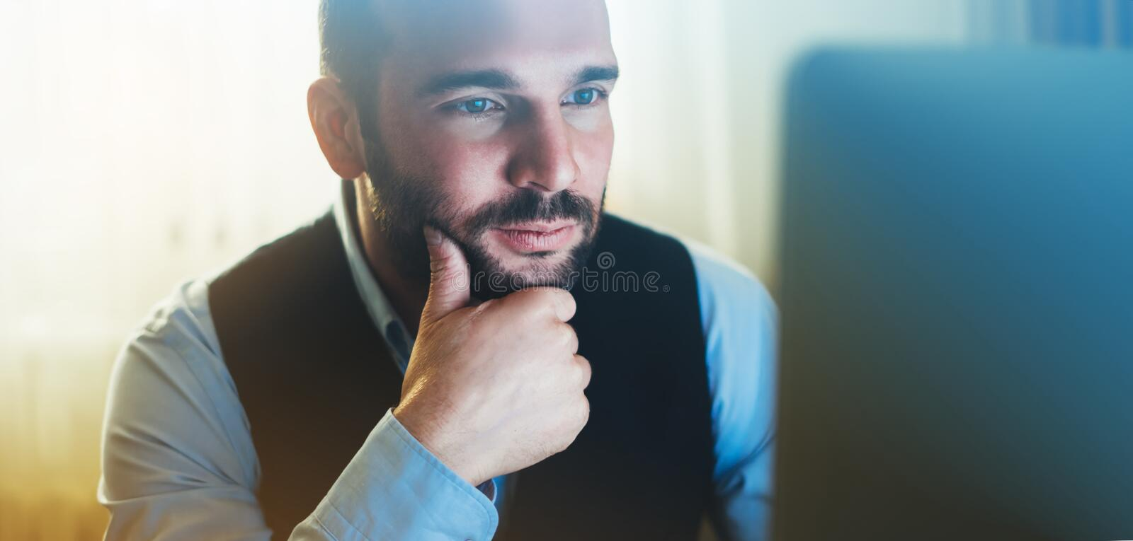 Bearded young businessman working on modern office. Consultant man thinking look in monitor computer. Manager typing on keyboard. Bearded young businessman stock photo