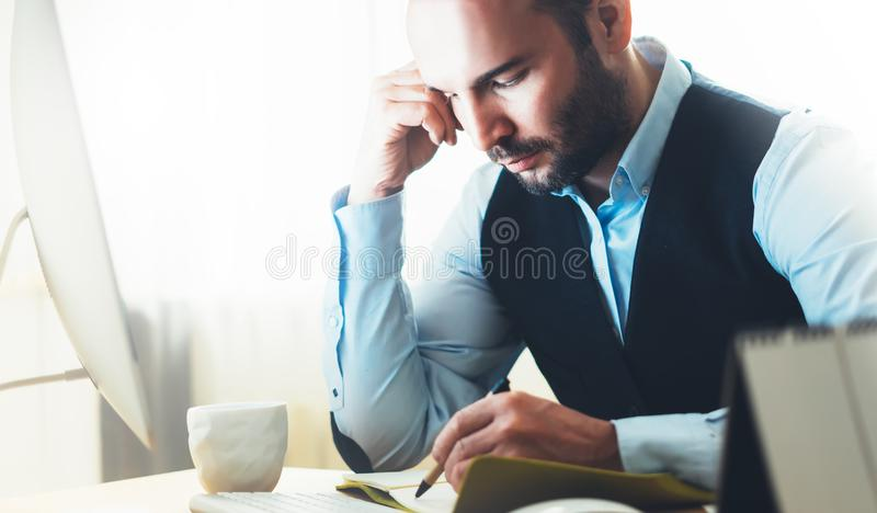 Bearded young businessman working on modern office. Consultant man thinking looking in monitor computer. Manager writes in noteboo. K in coworking workplace stock image