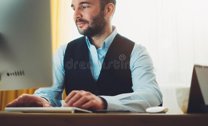 Bearded young businessman working on modern office at night. Consultant man thinking looking in monitor computer. Manager typing o royalty free stock photography