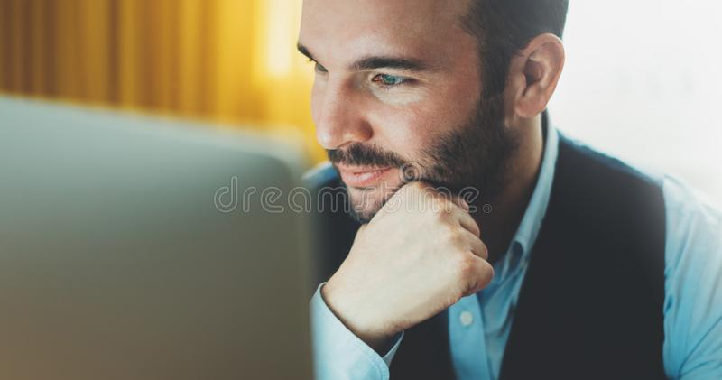 Bearded young businessman working on modern office at night. Consultant man thinking looking in monitor computer. Manager typing royalty free stock images