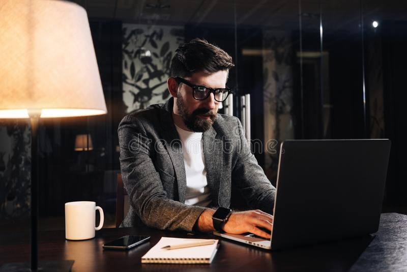 Bearded young coworker typing text on modern laptop in loft office at night. Businessman working process. Man using contemporary n royalty free stock photography