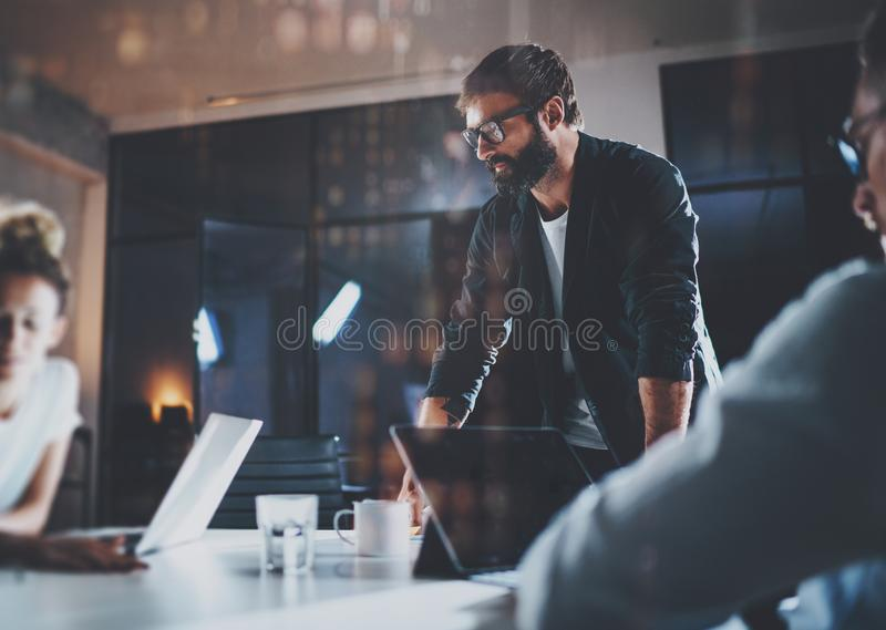 Bearded young coworker working at night office with partners.People using contemporary laptop and modern smartphone. Horizontal.Blurred background stock photos