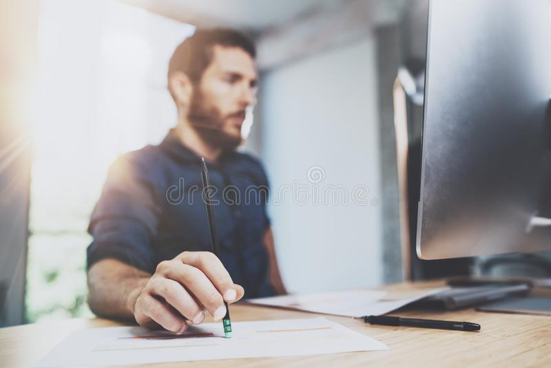 Bearded young coworker working at sunny office. Man using contemporary desktop computer and making notes in notebook. Horizontal. Blurred background stock photography