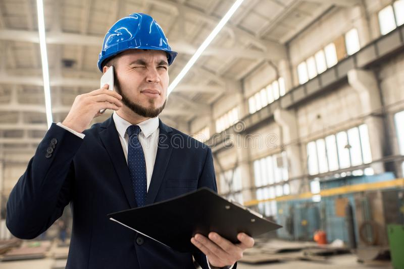 Tense Telephone Conversation with Business Partner. Bearded young entrepreneur wearing hardhat and classical suit talking to his business partner on mobile phone stock photo