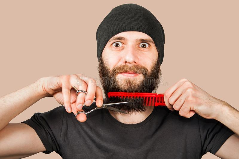 Bearded young guy in hat with comb and scissors cut his beard. Isolated on brown background stock image