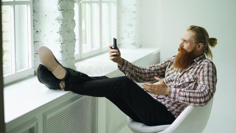 Bearded young hipster businessman talking video chat on smartphone while sitting in offce chair with his legs on royalty free stock image