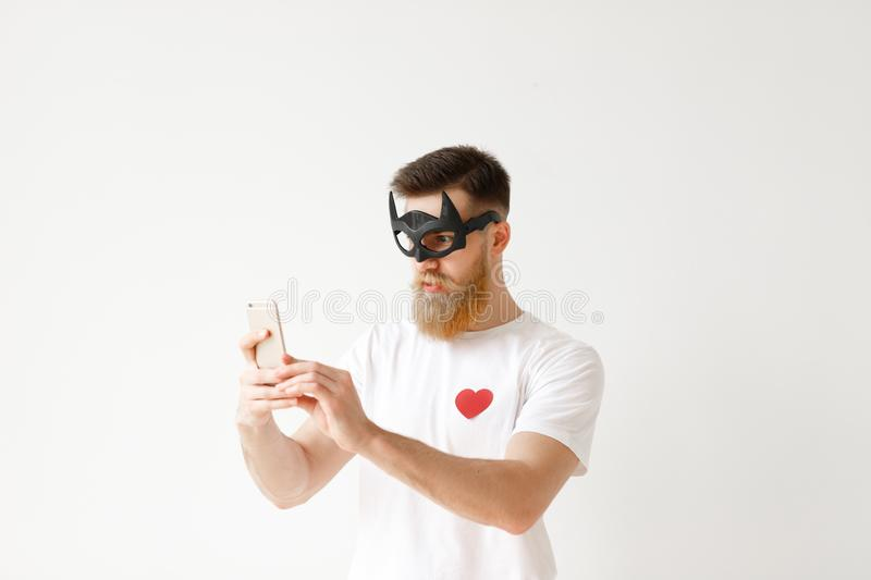 Bearded young male wears batman mask, uses smart phone for making photo, poses against white blank studio wall. Handsome royalty free stock photography