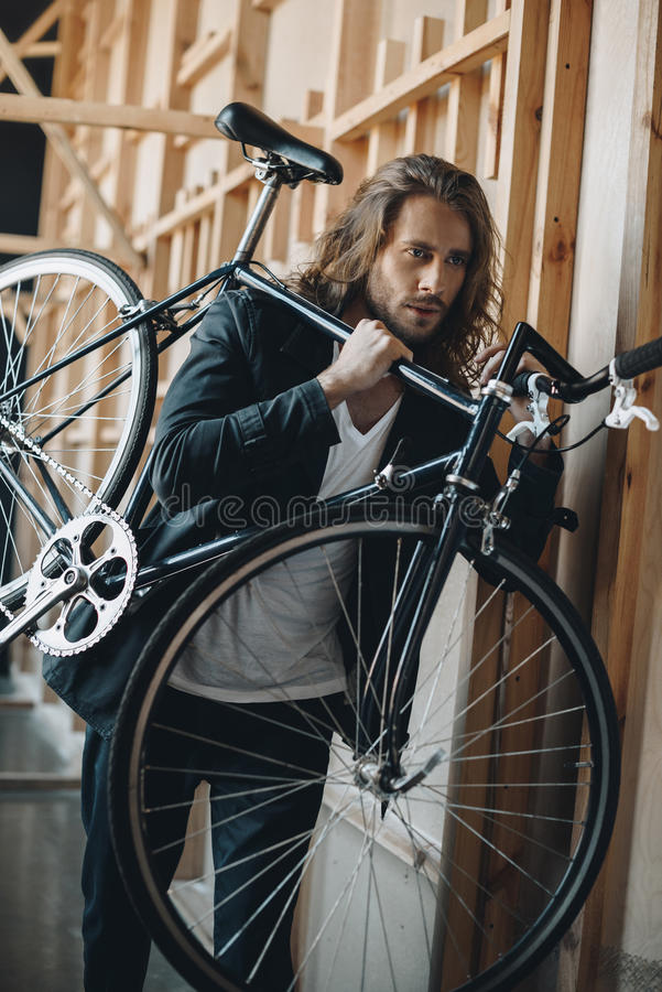 Bearded young man with long hair carrying bicycle on shoulder stock images