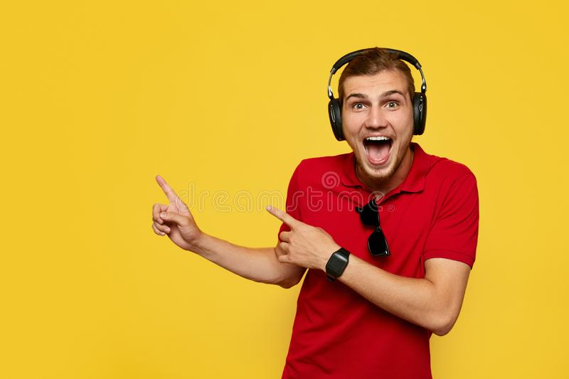 Bearded young man in red polo shirt and headphones pointing away and smiling on yellow background. Excited young man in red polo shirts and headphones pointing stock image