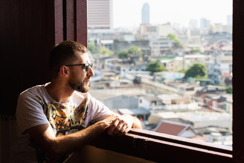 Bearded young man with sunglasses looking out of Golden Mount Wat Saket temple window over Bangkok, Thailand. Southeast asia oriental travel traditional tourism stock photos