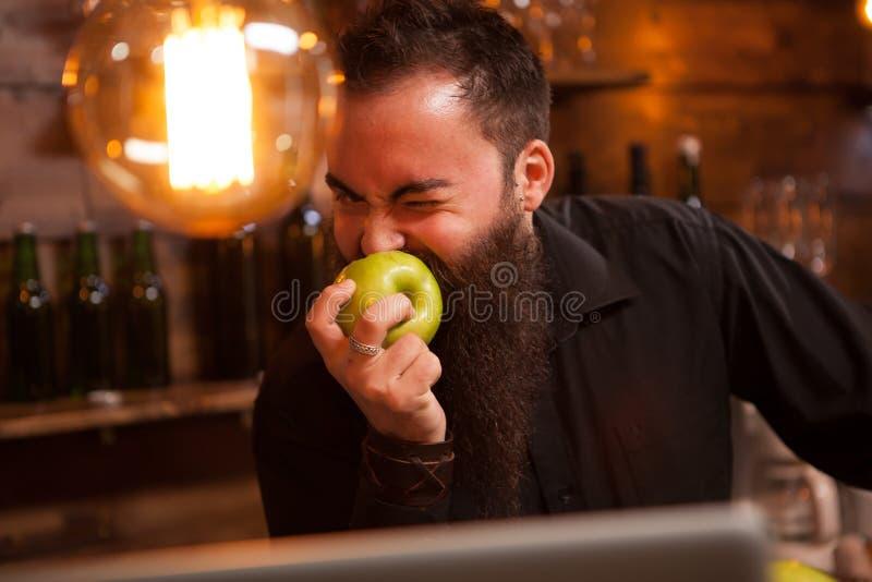 Bearderd barman je zielonego jabłka w rocznika pubie zdjęcia royalty free
