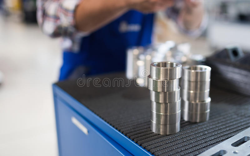 Bearings in industry factory with worker in background. Bearings in metal industry factory with worker in background royalty free stock photo