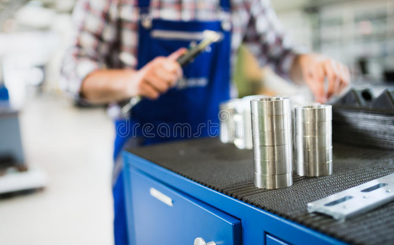 Bearings in industry factory with worker in background. Bearings in metal industry factory with worker in background stock image