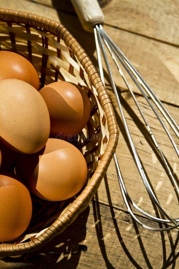 Beater και καλάθια των αυγών στο ξύλινο υπόβαθρο στοκ φωτογραφία με δικαίωμα ελεύθερης χρήσης