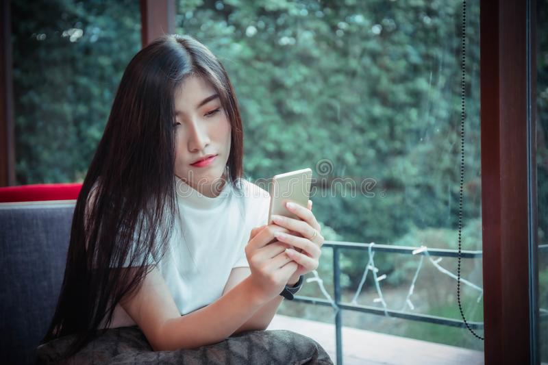 Beatiful asian girl`s holding mobile and have emotion happy looking at mobile phone.  royalty free stock images