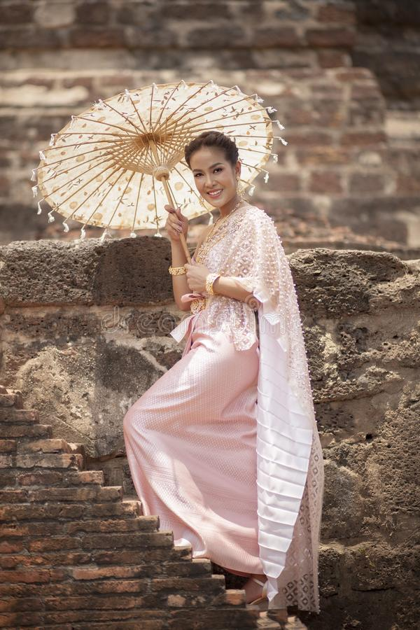 beatiful asian woman wearing thai traditon clothes style with wood umbrella toothy smiling standing in ayutthaya heritage place royalty free stock photos