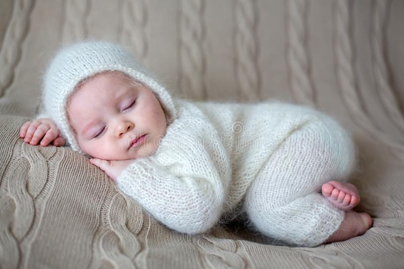 Beatiful baby boy in white knitted cloths and hat, sleeping. Sweetly posed in bed royalty free stock photos