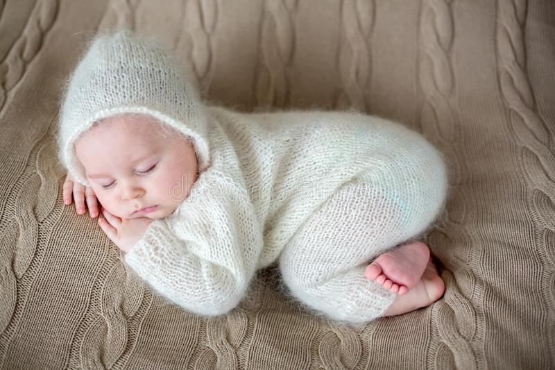Beatiful baby boy in white knitted cloths and hat, sleeping. Sweetly posed in bed stock images