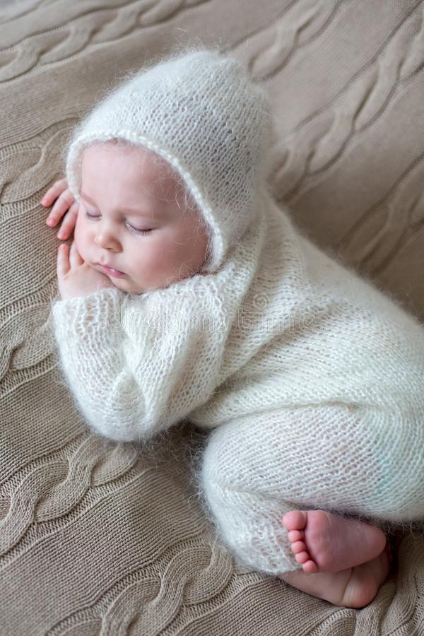 Beatiful baby boy in white knitted cloths and hat, sleeping. Sweetly posed in bed stock photos